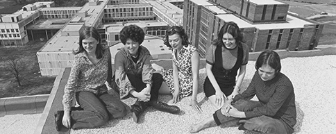 Photo from the 1970s of a group of students sitting on a roof-top