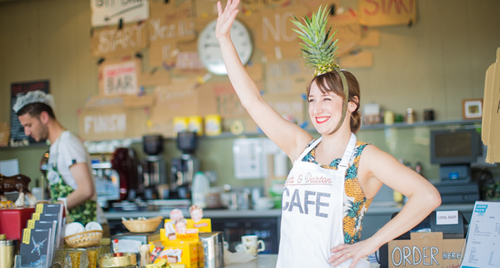 Woman with pineapple on her head waving in Lakeside Theatre Cafe