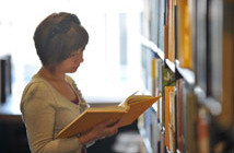 Student browsing books on library shelves